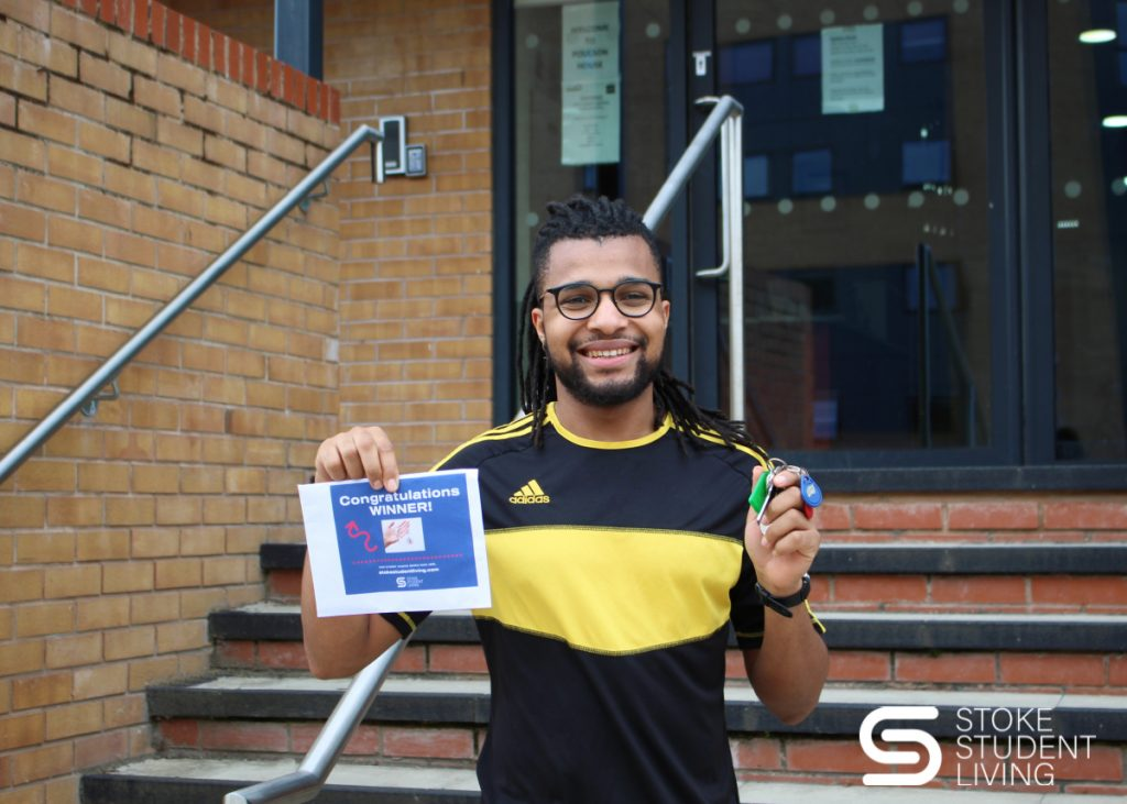 Winner of Stoke Student Living 'Years Free Rent competition' holding up keys to new apartment.