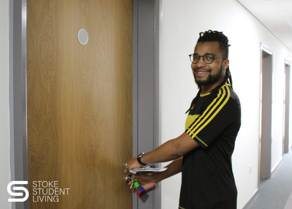 Winner of Stoke Student Living 'Years Free Rent competition' opening his new apartment door.